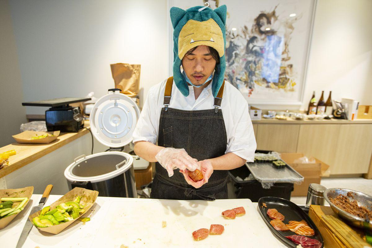 A sushi chef wearing a dark denim apron forms sushi.