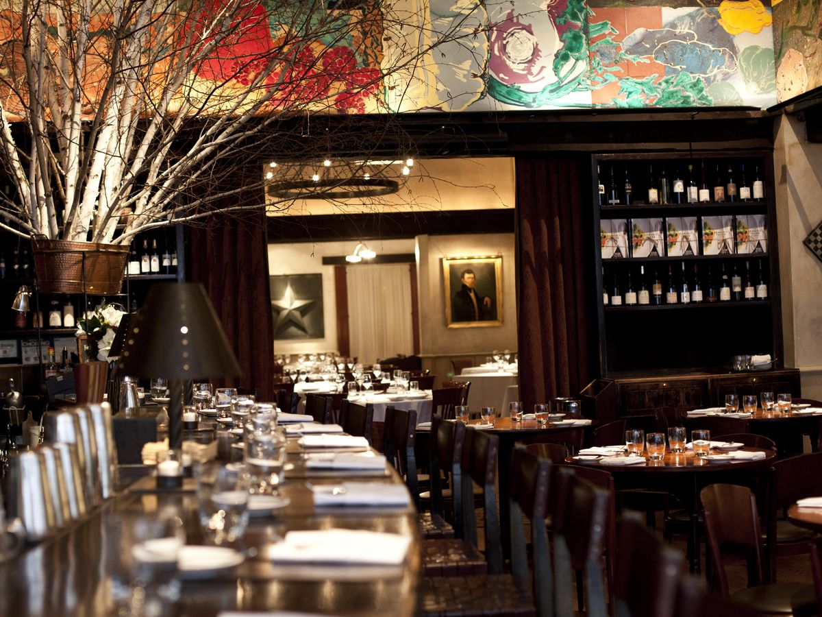 The barroom and dining room inside a dimly lit restaurant