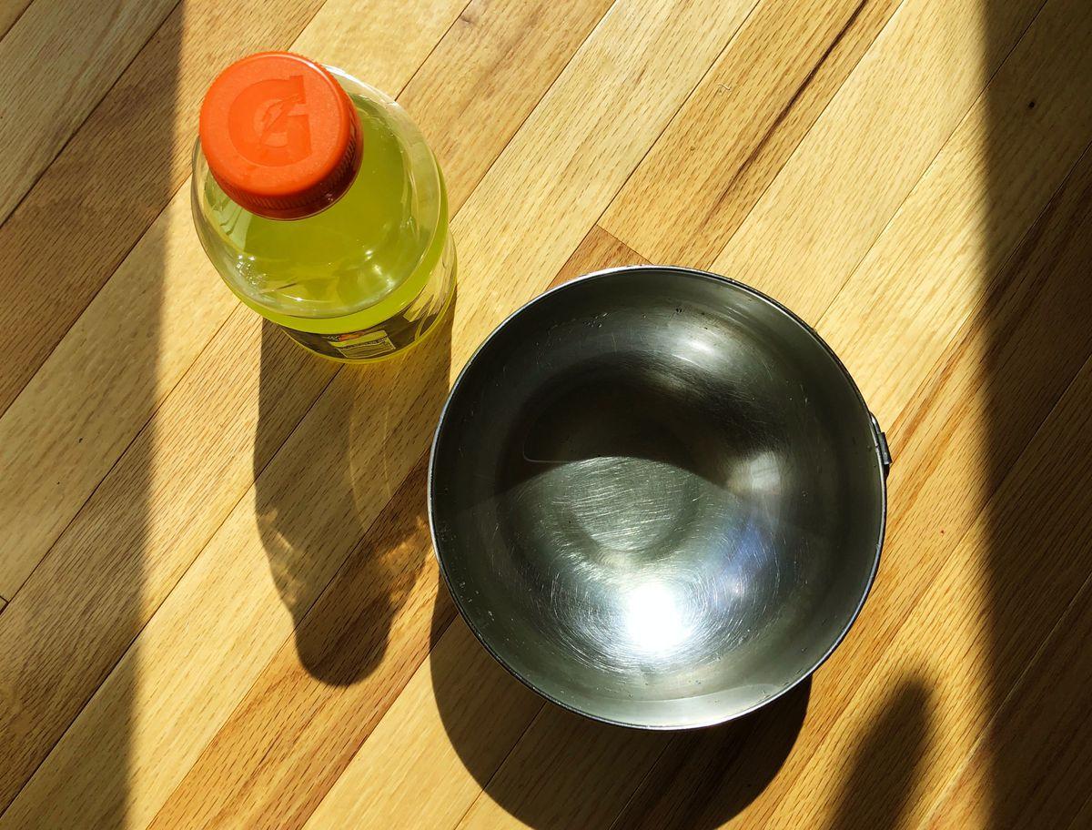 A bowl next to a yellow Gatorade.