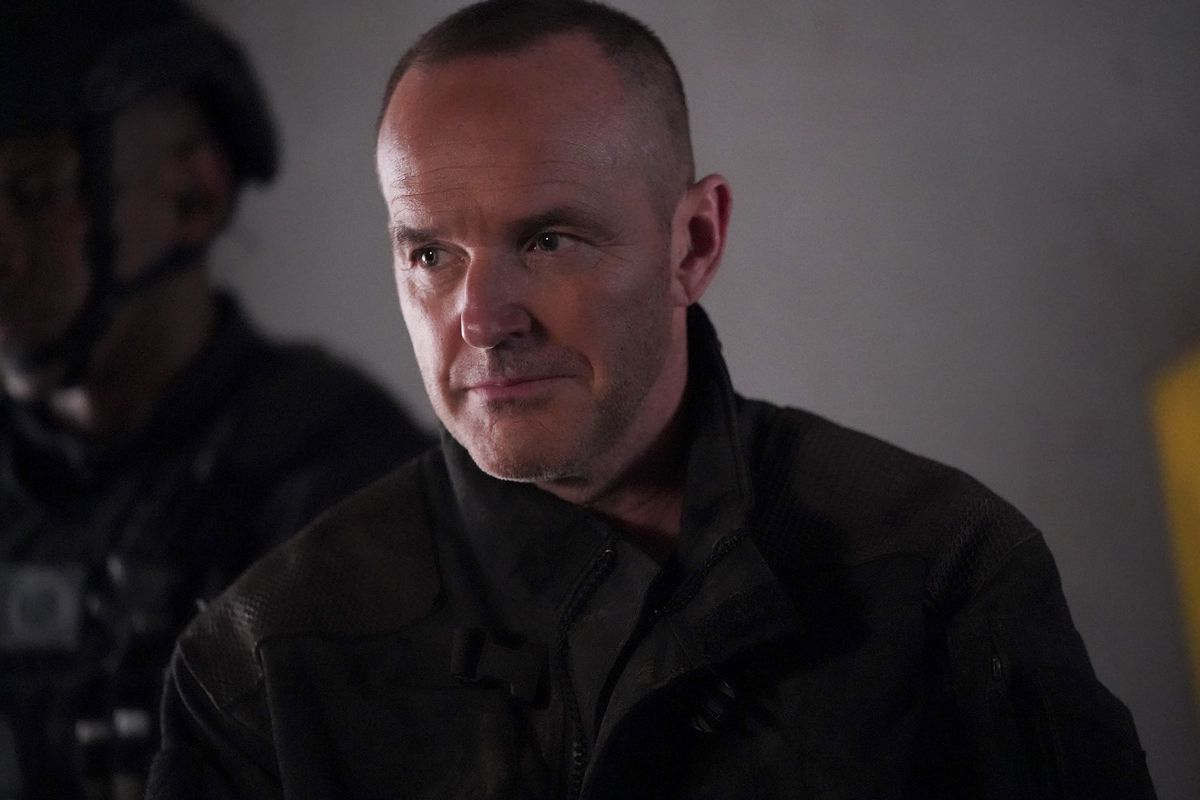 A man with a buzzed head — Sarge, an Agent Coulson lookalike — looks pensively to the side while wearing a brown jacket. A soldier in a helmet and combat gear stands in the background.