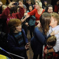Ruth and Kim Hackerford-Peer kiss after being married as their kids Riley and Casey watch in the Salt Lake County offices after a federal judge ruled that Amendment 3, Utah's same-sex marriage ban, is unconstitutional on Friday, Dec. 20, 2013.