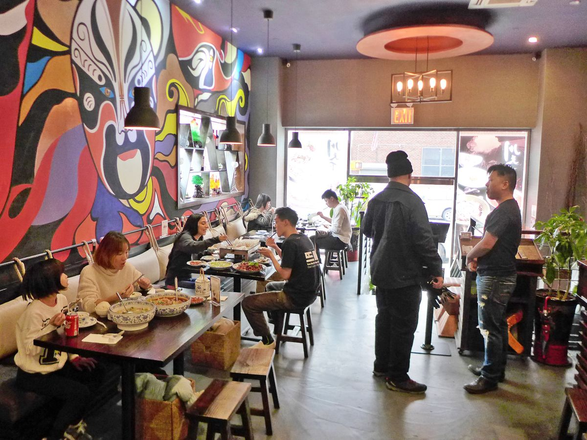 A row of tables with a mural behind it featuring colorful masks.