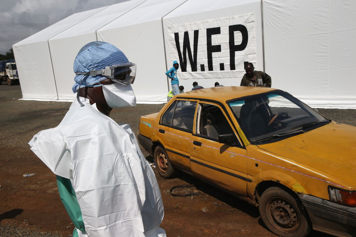 A Doctors Without Borders (MSF) staffer stands by as people arrive, requesting to be tested for the Ebola virus near Monrovia, Liberia.