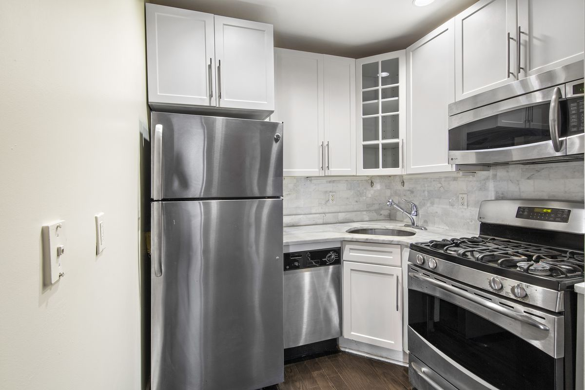 A kitchen with white cabinetry and grey tiles.