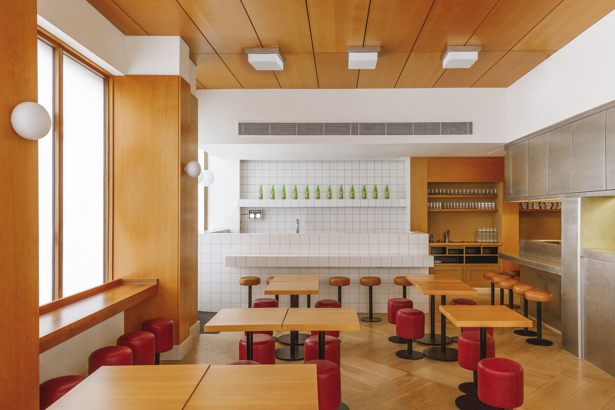 A restaurant interior with white tiling, red leather stools, and light, mid-century wooden tables