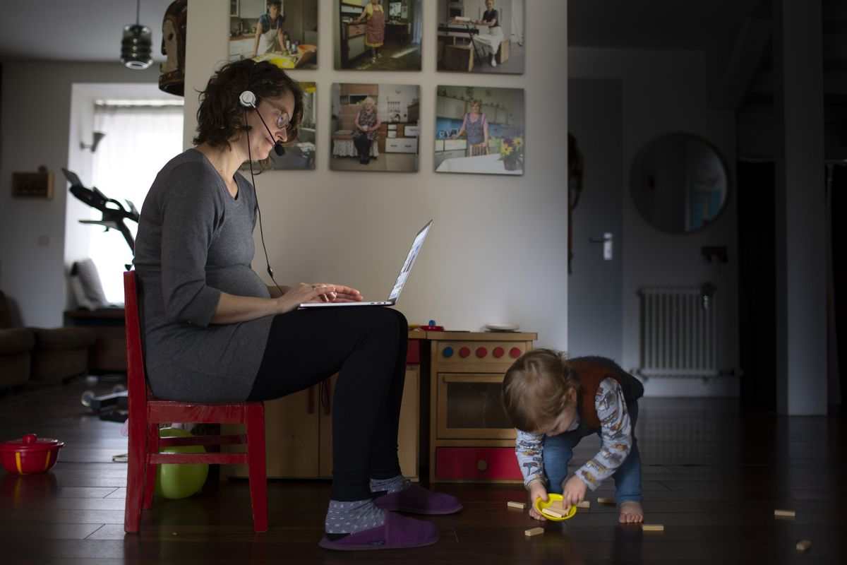 An adult working from home in the same room as a toddler.