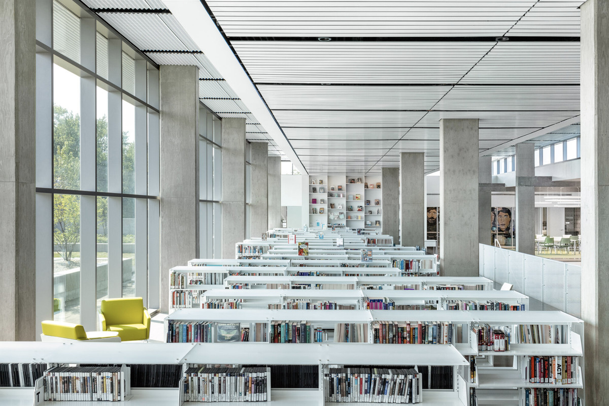 Stacks of books next to windows and tall concrete columns on white shelves.