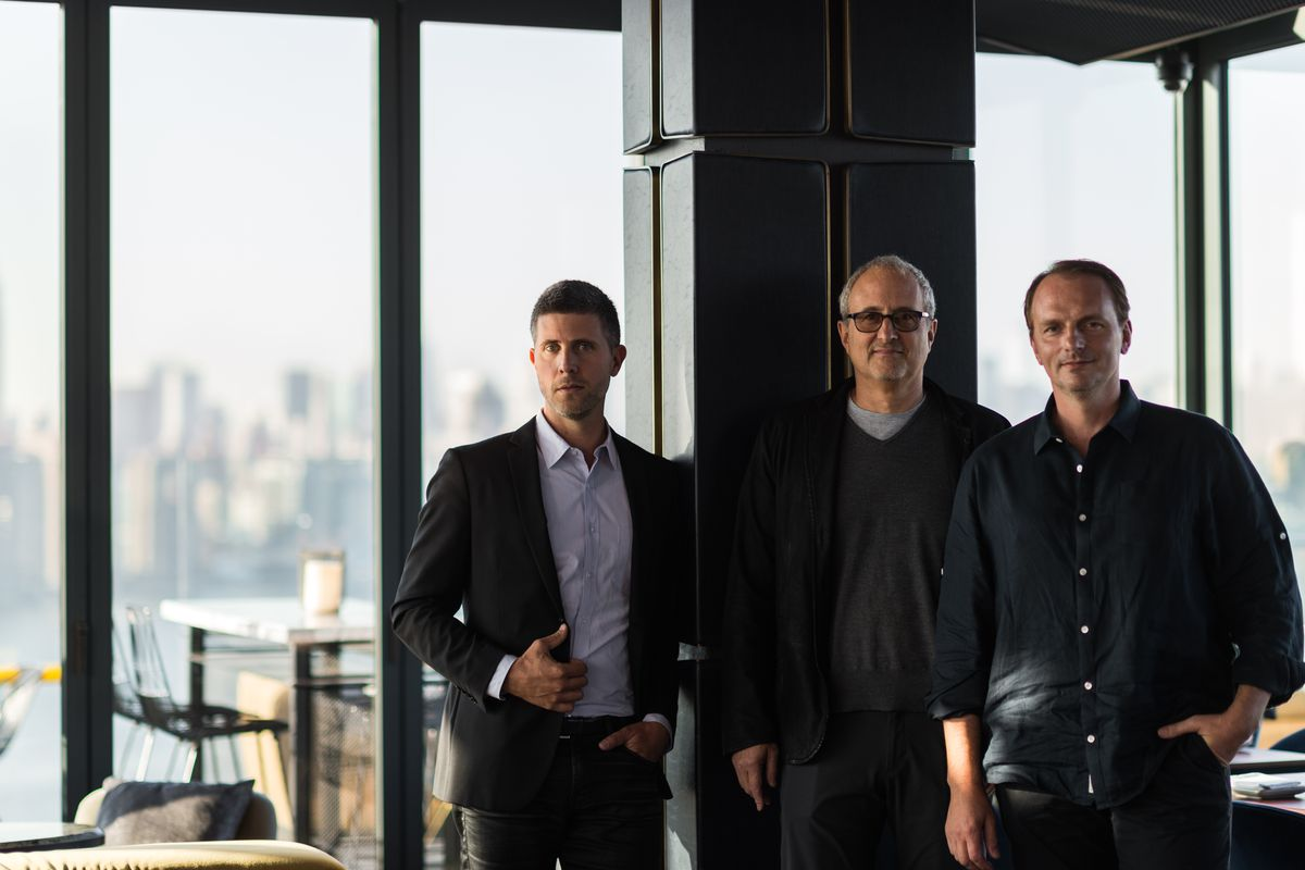 A photo of partners Luke Ostrom, Josh Pickard, and Andrew Carmellini, all dressed in dark colors and standing in front of windows with a view of Manhattan