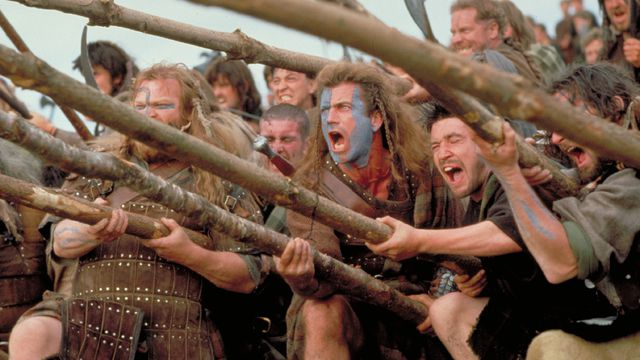 william wallace and a bunch of scotsmen hold spears and scream in braveheart