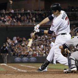 Minnesota Twins' Joe Mauer hits an RBI single in the seventh inning of a baseball game, as the Twins came from behind to beat the New York Yankees 5-4 in a baseball game Tuesday, Sept. 25, 2012 in Minneapolis. At right is Yankees catcher Russell Martin who had a solo home run in the game.