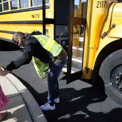 In this photo taken Aug. 18, 2012, Sharon Beal, right, a bus monitor in the district for 25 years, greets a student during a bus orientation open house for parents and students riding the bus for the first time this school year, at the Buffalo Academy for Visual and Performing Arts, in Buffalo, N.Y. The cell phone video of a bus monitor's cruel taunting, in June, ignited a global outpouring of support for the monitor and revulsion at her middle-school tormentors. The video raised questions about the role of bus monitors, including how much they can really do to protect against bullies while seeing riders safely on and off the bus, and how its victim, the authority figure on the bus, could command so little respect.