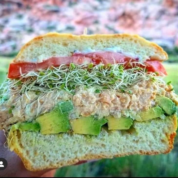 A sandwich with tomato, alfalfa sprouts, tuna, and avocado