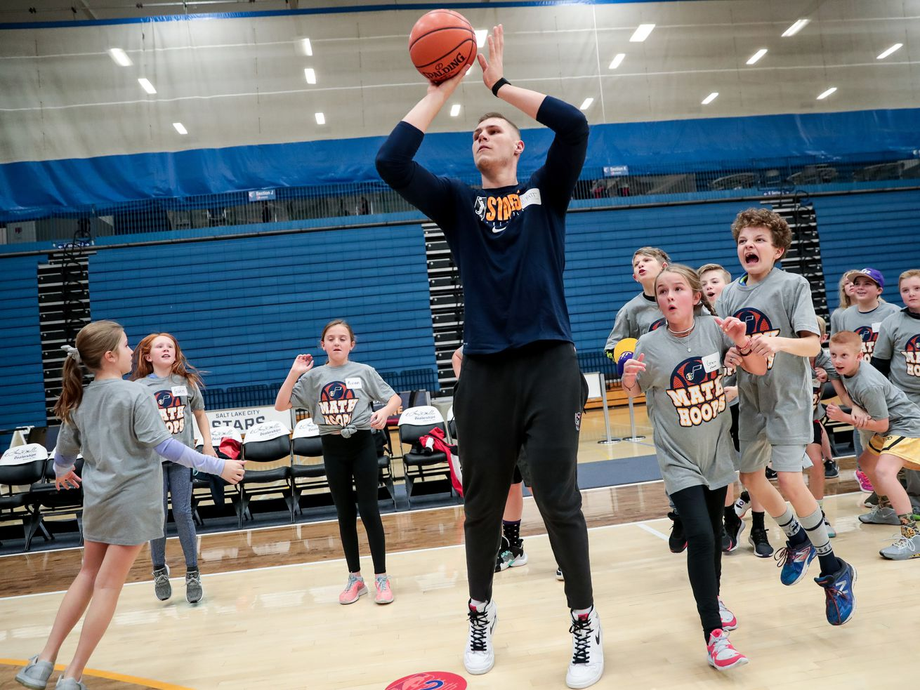 Salt Lake City Stars forward Wyatt Walker shoots as Grace Mower, 10, second from right, Jonathan Welch, 11, right, and other students from Carden Memorial School in Salt Lake City cheer him on during an NBA Math Hoops Live event at Salt Lake Community College's Bruin Arena in Taylorsville on Tuesday, Jan. 14, 2020.