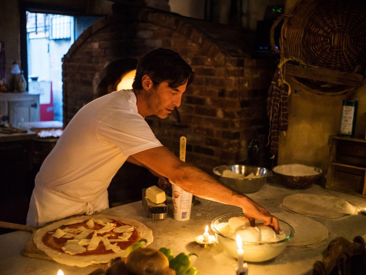 A man makes pizza at a counter.
