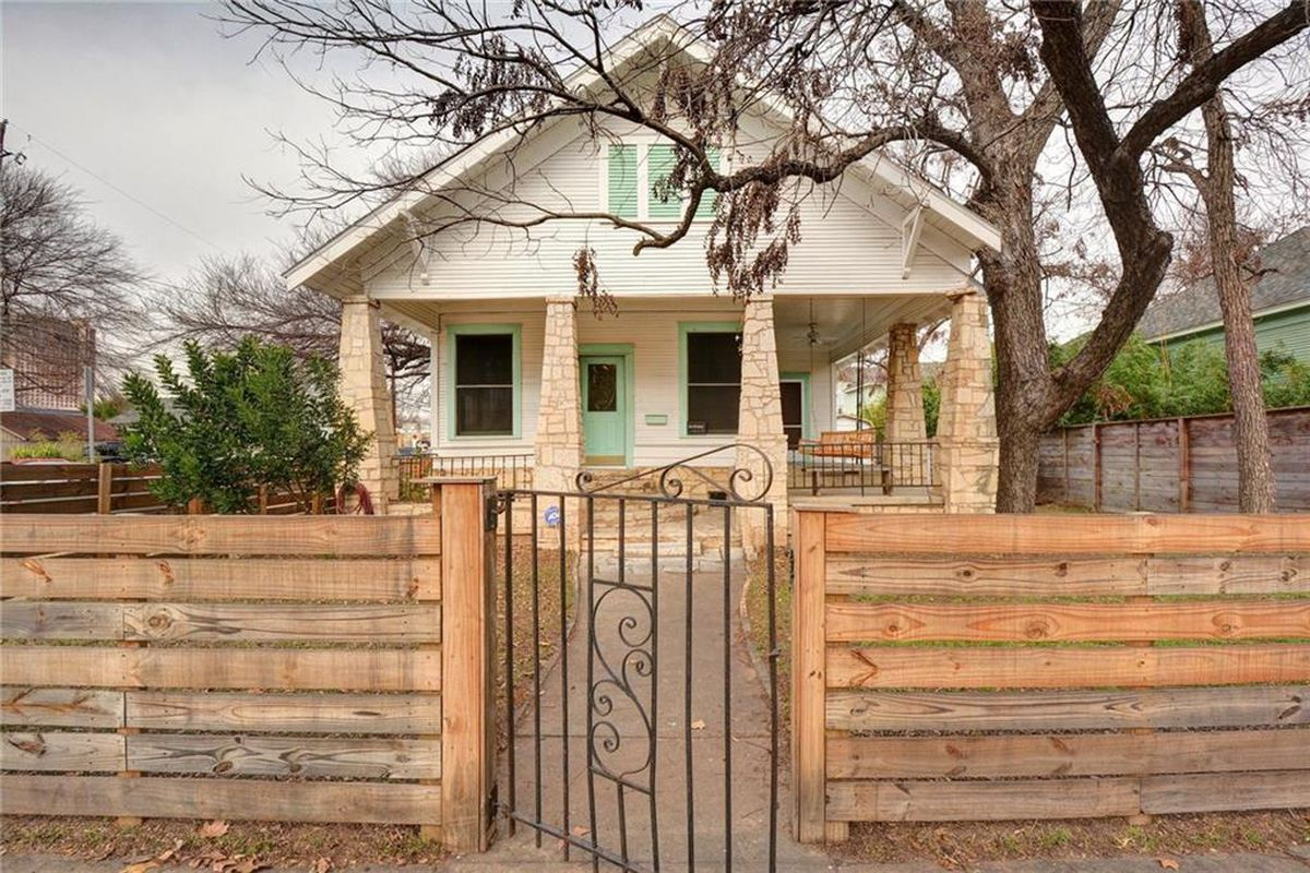 White and light green  1935 Craftsman with stone porch pillars and fence in front