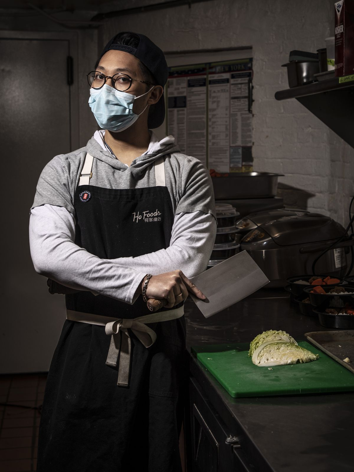 The cook Trevor Liu wore a face mask and held a knife in the kitchen at Ho Foods
