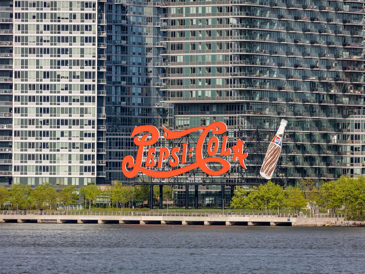 """A red, neon sign situated on a waterfront in front of buildings. The sign reads """"Pepsi-Cola"""" and has a large bottle next to it."""