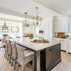 Removing several partition walls created space for an open-plan kitchen/dining area. The kitchen island serves as a center for food prep and casual eating and drinking. Gold light fixtures echo gold accents in the black finish on the kitchen island cabinets.