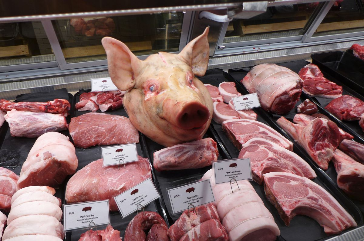 A lush display of meats, with a pig head in the middle.