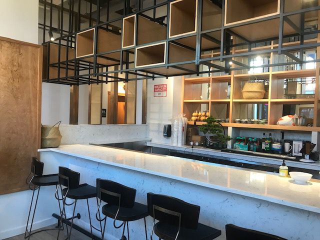 The empty bar at Chengdu Taste with a white marble top and black chairs
