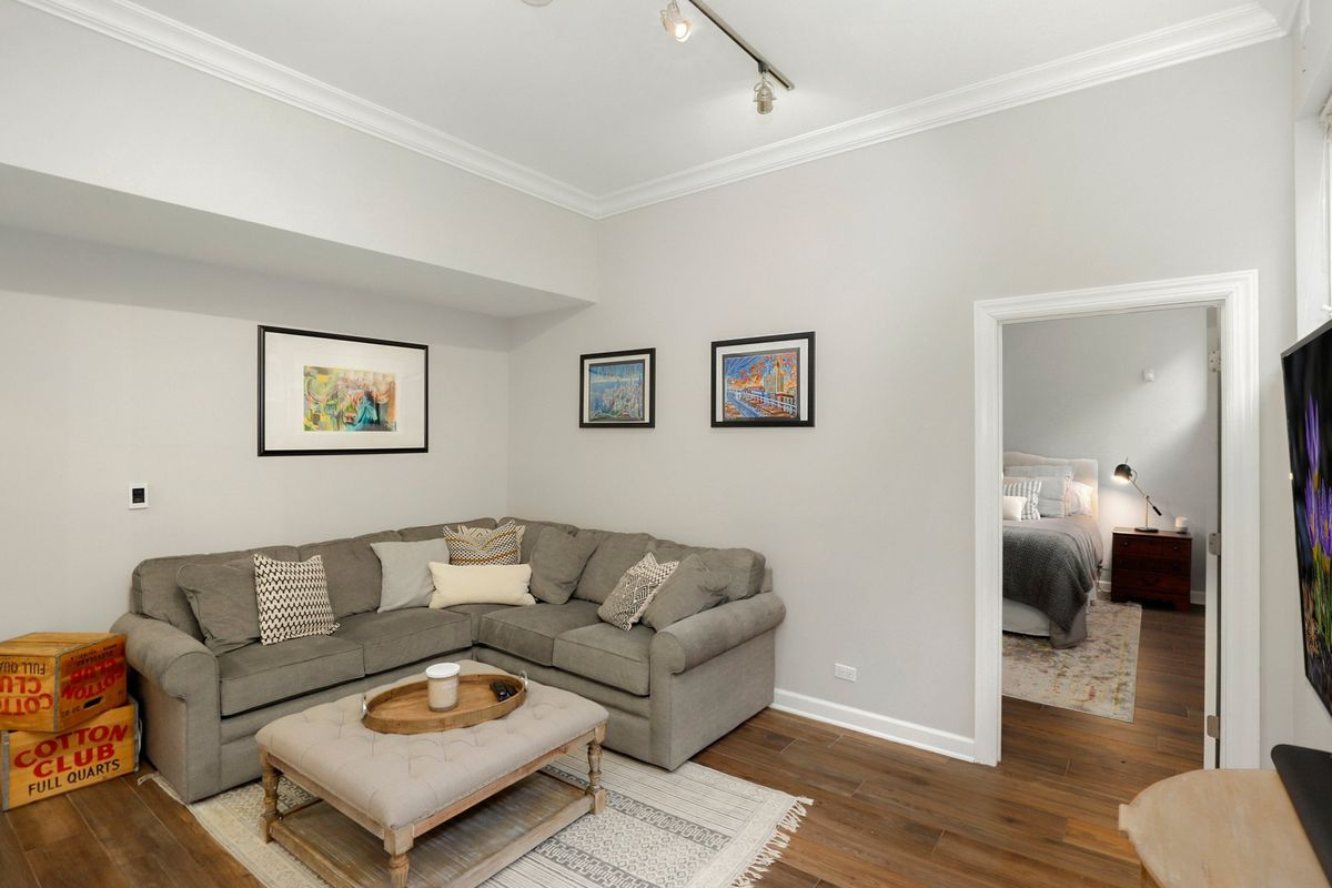 The lower level family room and bedroom. There is a grey corner couch, track lighting, and a few framed photos.