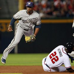 Milwaukee Brewers second baseman Rickie Weeks (23) avoids Atlanta Braves Jason Hayward while turning a double play on a Tyler Pastornicky ground ball in the fourth inning of a baseball game in Atlanta, Friday, April 13, 2012.