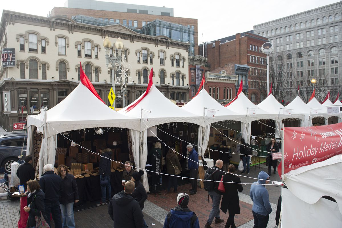 A holiday market with white tents in a downtown area. People browse and mill about.