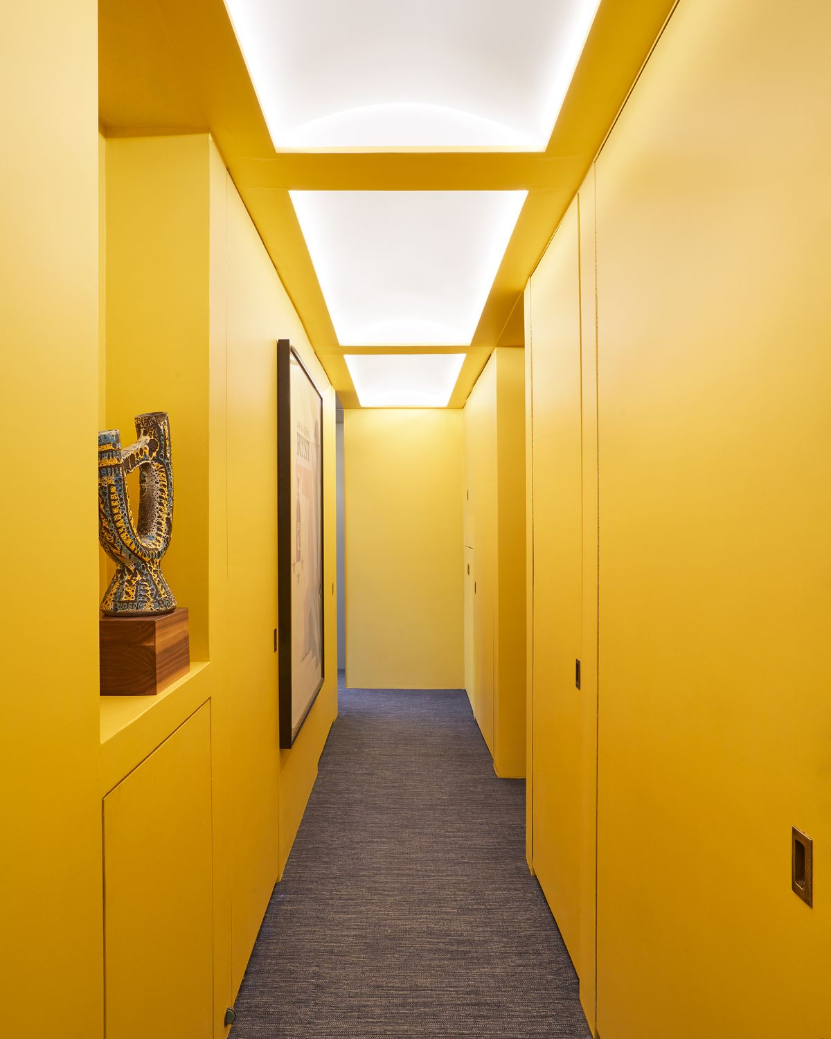 A bright yellow painted hallway with doors on both sides. There is a shelf on one side of the hallway with an ornate work of art sitting on it.