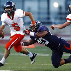 Mountain Crest's #5 Jamison Webb, left, avoids the rush of Woods Cross' #40 Collin Sauni in the second quarter of play Friday, Aug. 31, 2012.