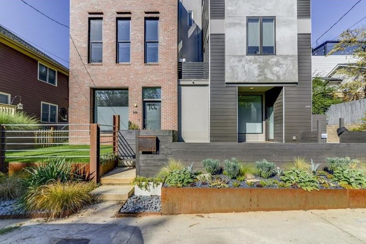 Three-story brick townhouse with small front yard.
