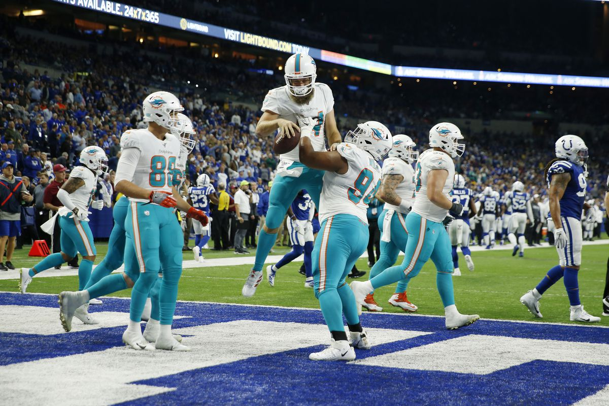 Miami Dolphins quarterback Ryan Fitzpatrick is congratulated by teammates after scoring a touchdown against the Indianapolis Colts during the second quarter at Lucas Oil Stadium.