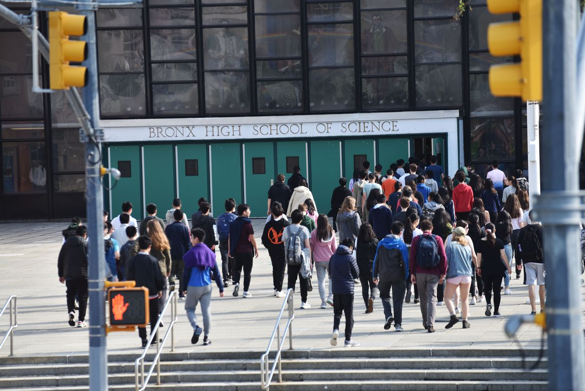 Several students walk toward the entrance of Bronx High School of Science in New York City. They are framed by two yellow traffic lights.