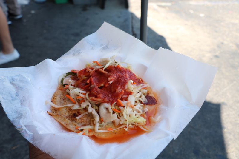 Pupusa topped with curtido with sauce at LA's Two Guys Plaza Salvadoran street market.