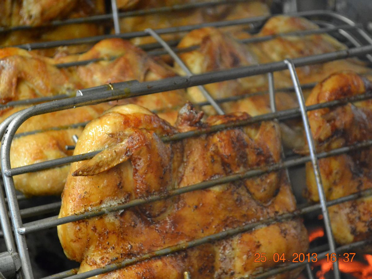 chicken spinning on charcoal grill