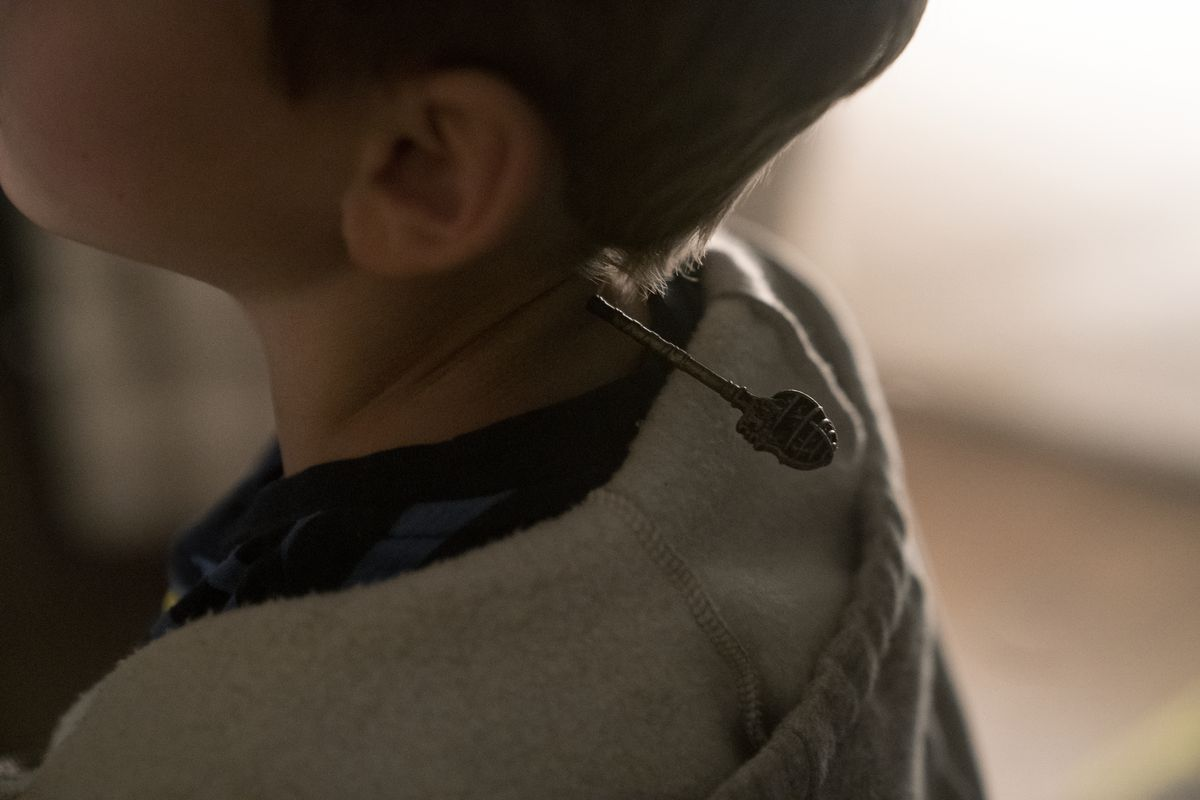 An elaborate key sticks out of the back of a fleshy keyhole in a character's neck in Netflix's Locke & Key.