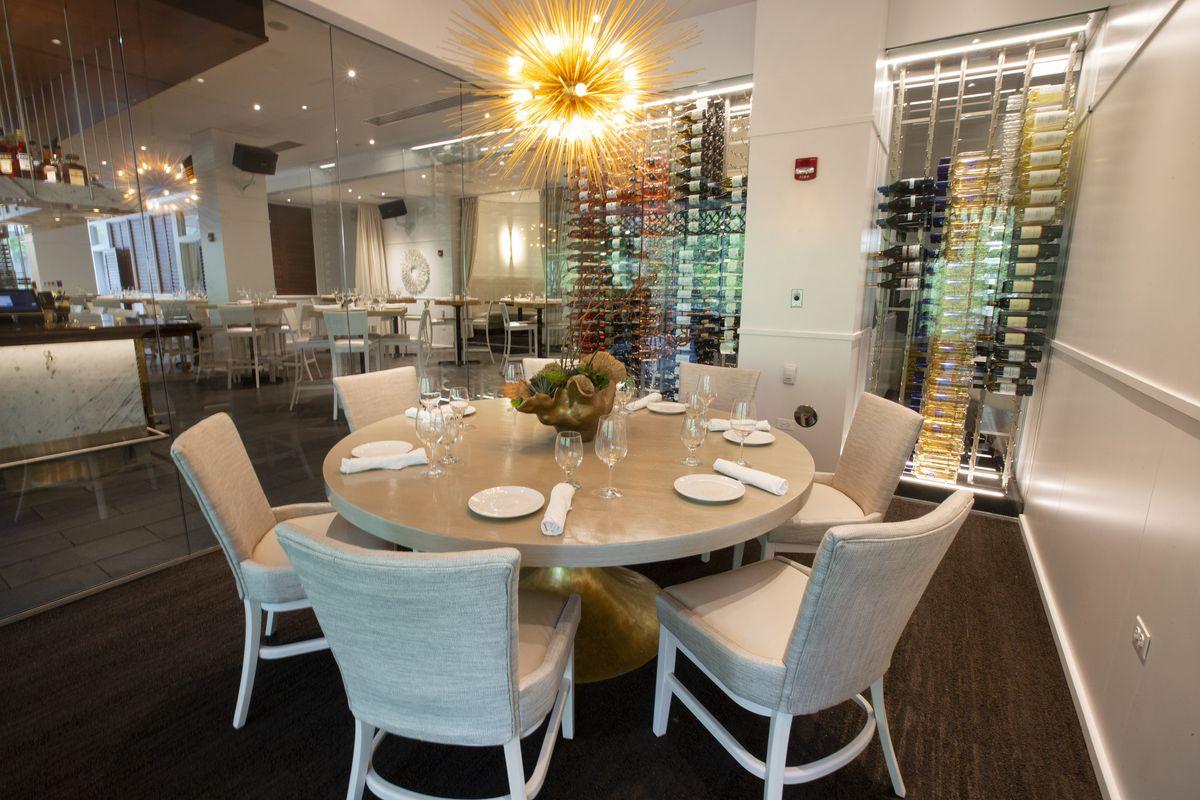 Τραπέζι και καρέκλες μέσα σε ένα γυάλινο δοχείο δίπλα σε σειρές μπουκαλιών κρασιού.