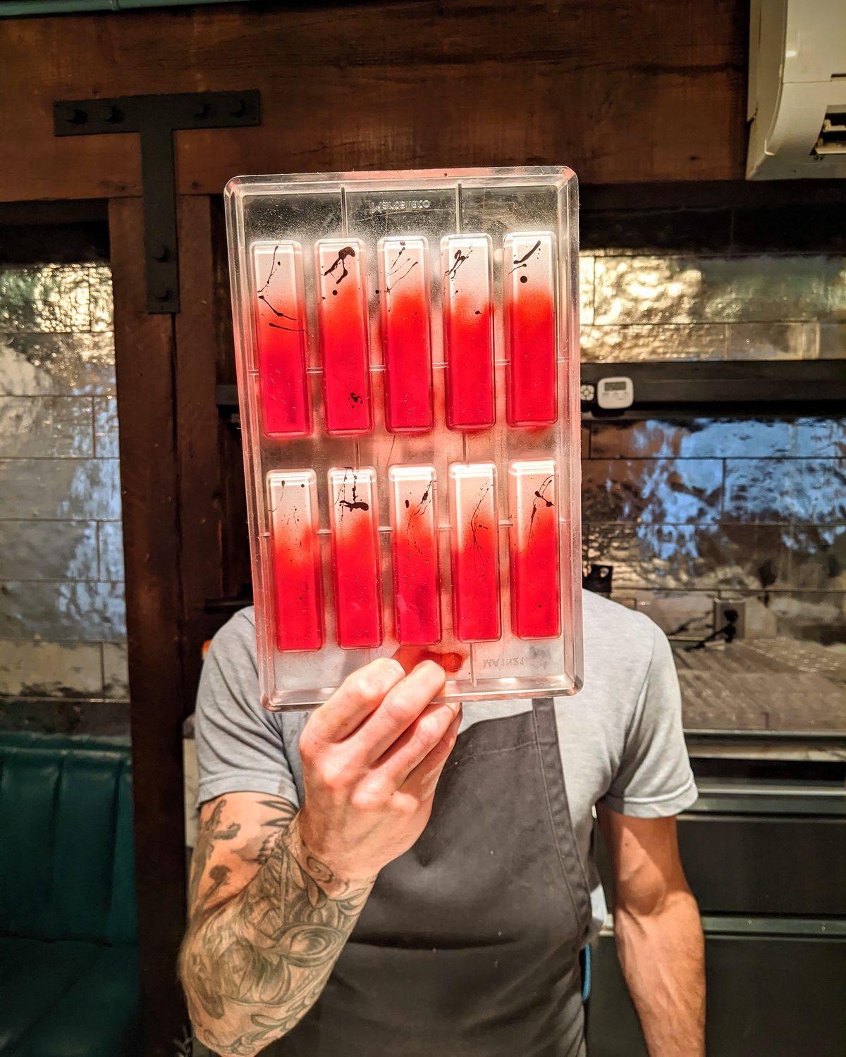 Simon Brown is holding a mold full of red and chocolate bars