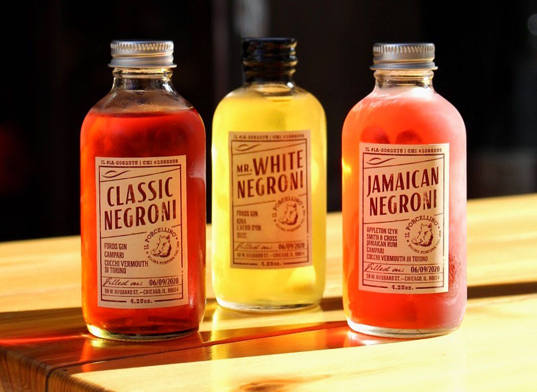 Three capped bottles filled with brightly colored cocktails