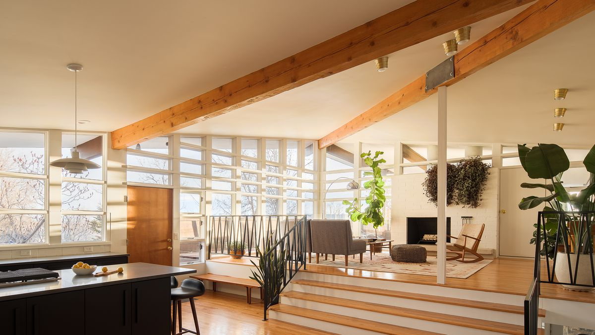 A living area. There are hardwood floors and on one wall there are floor to ceiling windows. The ceiling is off-white with wooden beams. There is a black kitchen island with stools. In the room next to the windows is a sitting area with various types of c
