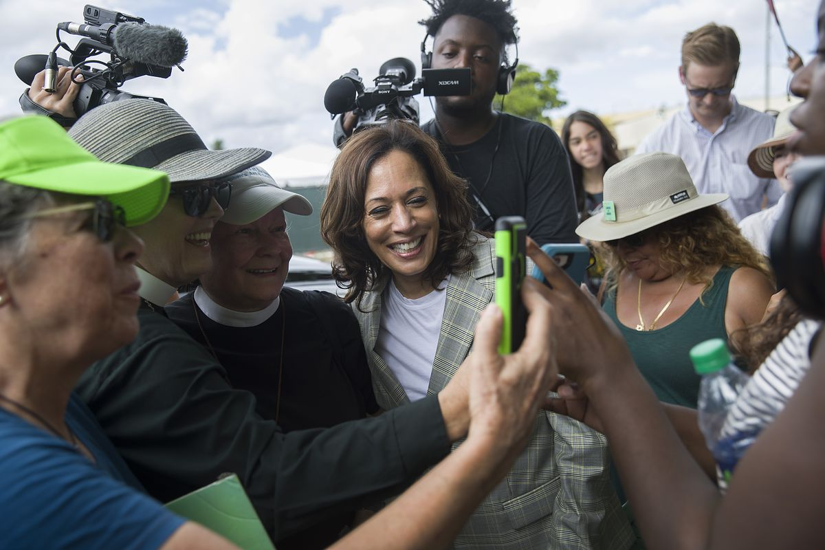 Democratic presidential candidate Kamala Harris in a group of reporters and civilians.