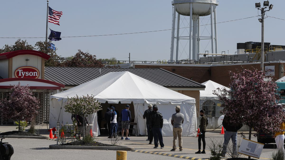 Line of people waiting outside a white pop-up tent in front of a Tyson water tower.