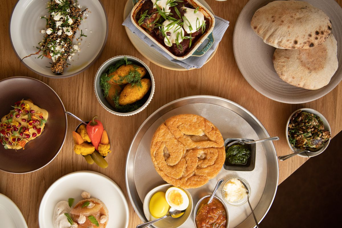 A spread of Galit's Middle Eastern dishes includes breads, toasts, hummus, pitas, charred vegetables, and more.