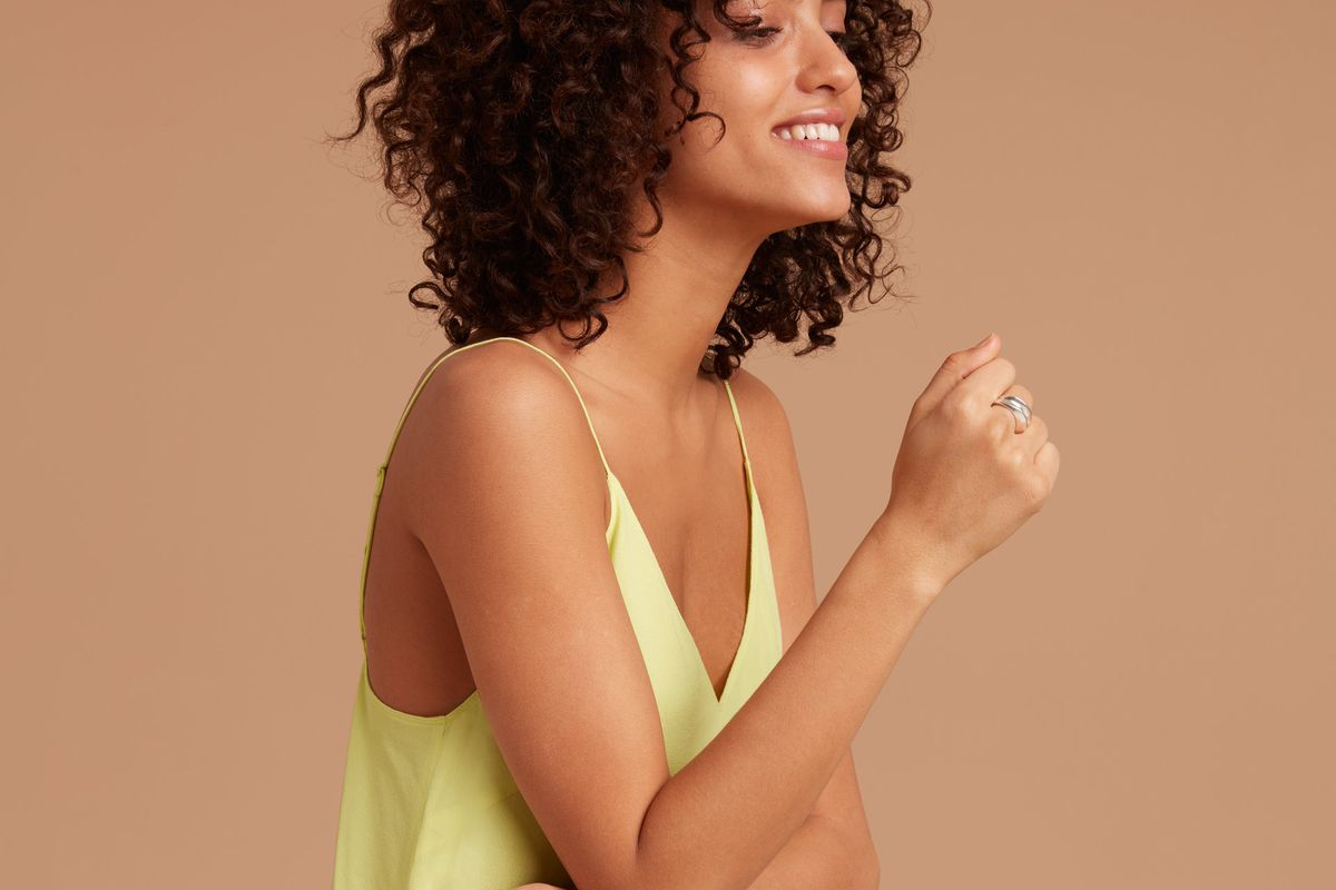 A model in a yellow slip dress