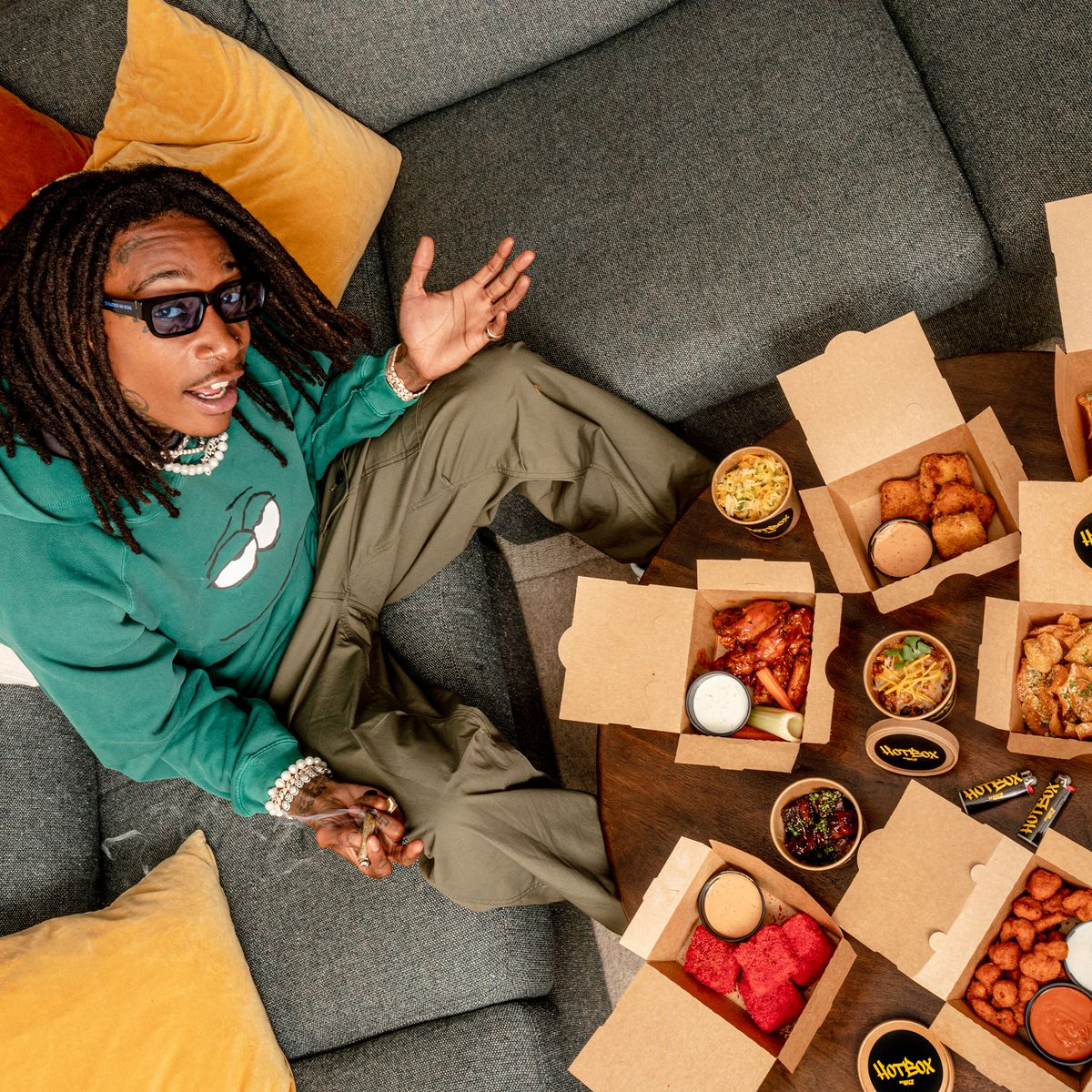 Rapper Wiz Khalifa sits on a grey couch in front of open boxes of food.