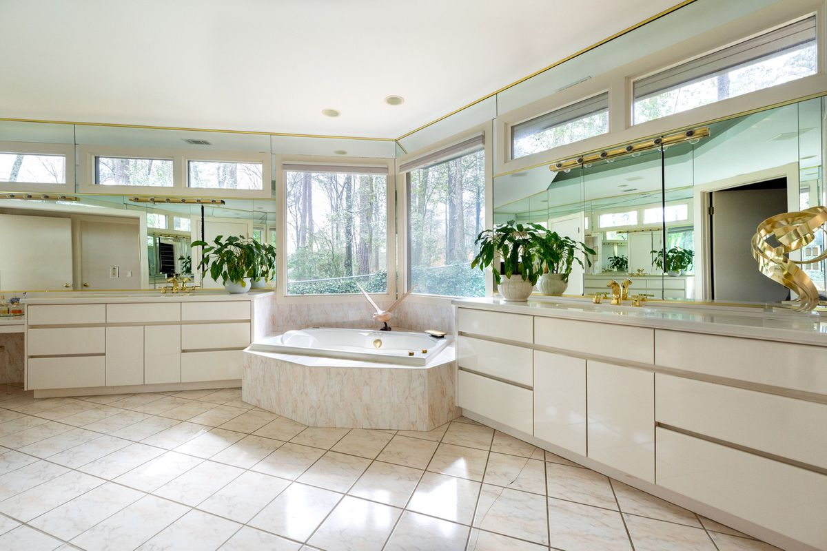A huge and dated white master bathroom.