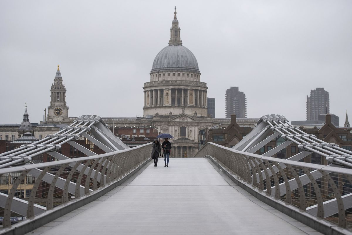 People walk across the Millennium Bridge in London, Monday Dec. 21, 2020. Millions of people in England have learned they must cancel their Christmas get-togethers and holiday shopping trips.
