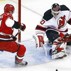 New Jersey Devils goalie Martin Brodeur (30) gathers in the puck in with the help of teammate Peter Harrold (10) with Carolina Hurricanes' Drayson Bowman (21)nearby during the second period of an NHL hockey game in Raleigh, N.C., Saturday, March 31, 2012. Devils won 5-0. (AP Photo/Karl B DeBlaker)