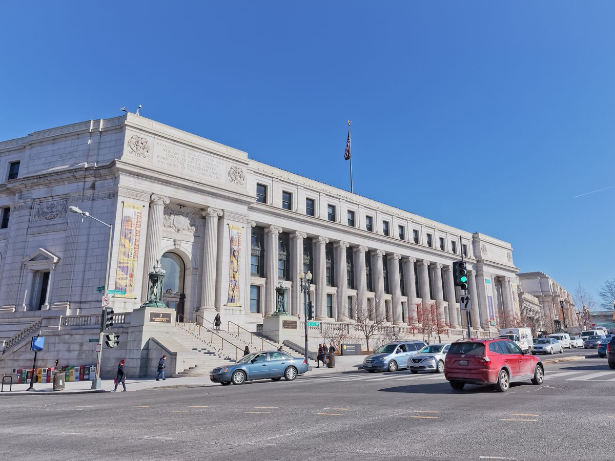 The exterior of the Smithsonian National Postal Museum. The facade is white with columns and an arched entryway.