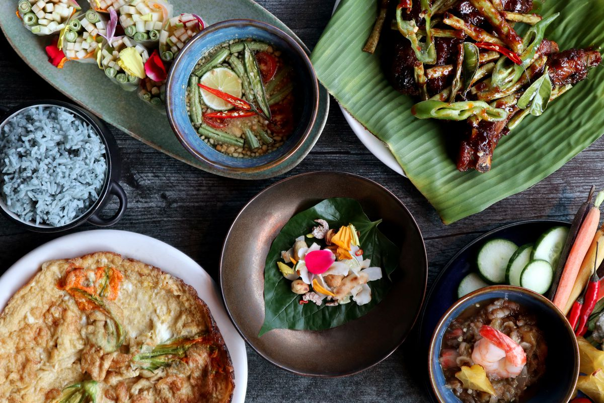 A colorful mix of seafood, meat, and vegetable dishes made by chef Hong Thaimee are laid out on a dark table.