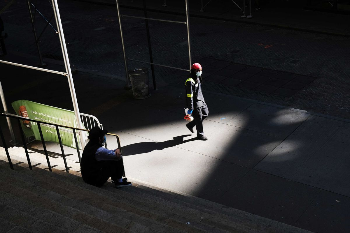 People walk by the New York Stock Exchange along Wall Street in New York City
